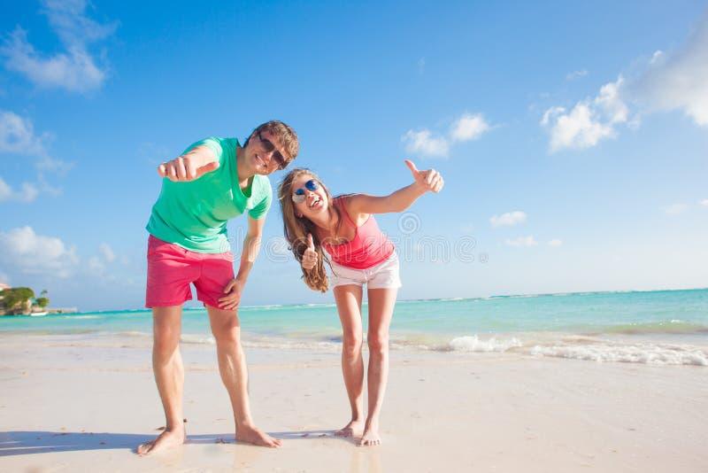 Hintere Ansicht von den glücklichen romantischen jungen Paaren, die auf dem Strand umarmen lizenzfreie stockfotografie