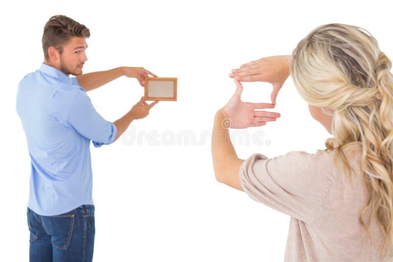 Hintere Ansicht von den jungen Paaren, die herauf Bilderrahmen hängen stockbilder