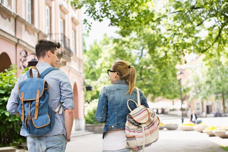Hintere Ansicht von den jungen sprechenden Collegefreunden beim Gehen in Campus stockfoto