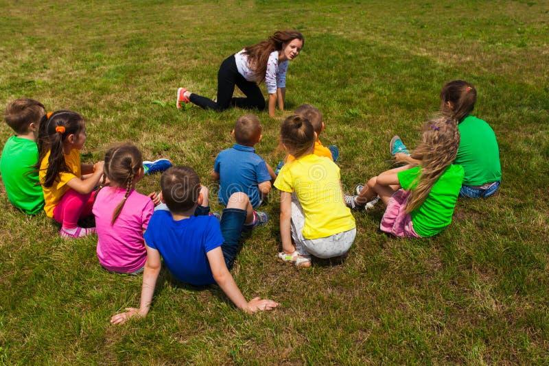 Hintere Ansicht von den Kindern, die auf einem Gras spielt Scharaden sitzen lizenzfreie stockfotos
