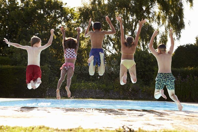 Hintere Ansicht von den Kindern, die in Swimmingpool im Freien springen stockfotografie