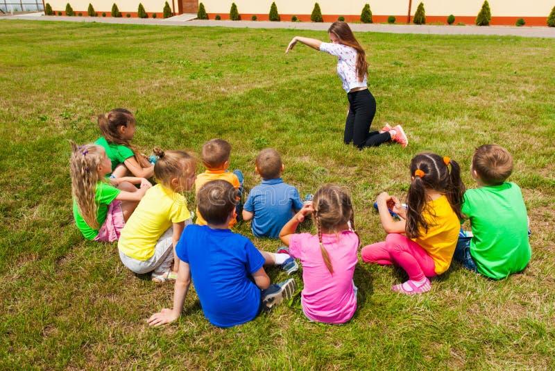 Hintere Ansicht von den Kindern, die Zeitaußenseite ausgeben und Scharaden spielen stockfotos