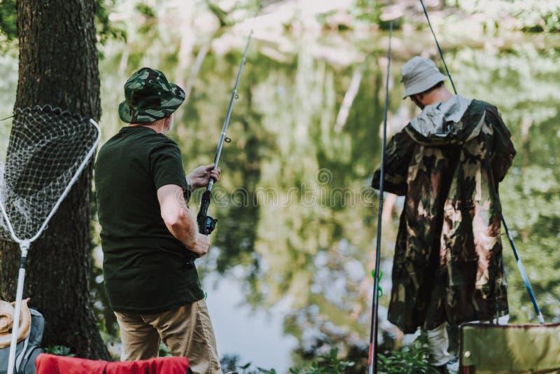 Hintere Ansicht von den Männern, die auf der Flussbank fischen stockfotos