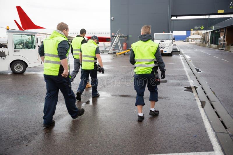 Hintere Ansicht von den männlichen Arbeitskräften, die auf nasse Rollbahn gehen stockfotos