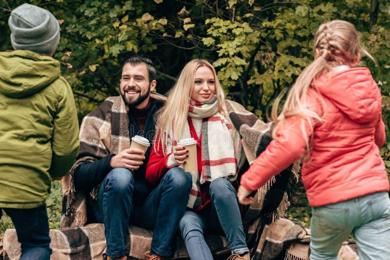 hintere Ansicht von den netten Kleinkindern, die zu den glücklichen Eltern trinken Kaffee laufen lizenzfreies stockbild