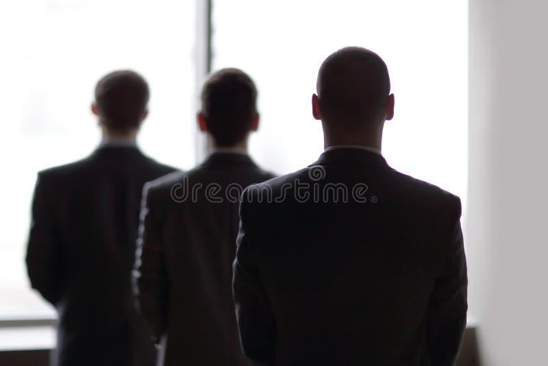 Hintere Ansicht von drei Geschäftsmännern, wie sie entlang des großen Fensters anstarren, welches die Stadt übersieht lizenzfreies stockbild