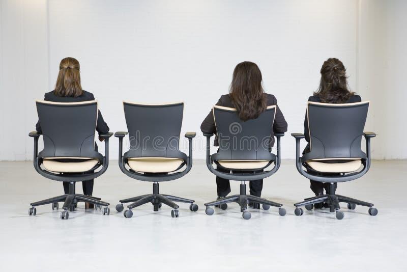 Hintere Ansicht von drei Geschäftsfrauen, die in einem Lin sitzen lizenzfreies stockbild