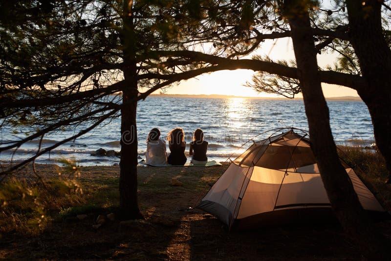 Hintere Ansicht von drei touristischen Mädchen, die auf Seeufer vor dem Zelt genießt schönen Sonnenuntergang sitzen lizenzfreie stockbilder