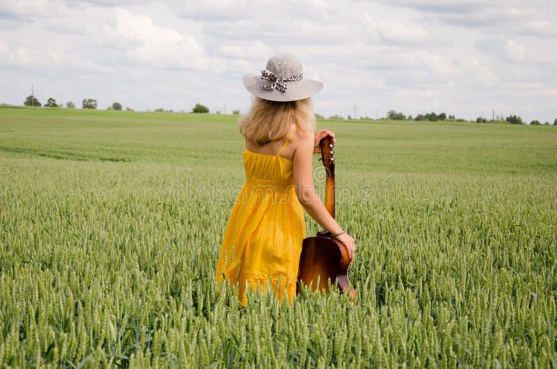 Hintere Ansicht von Frauen mit Gitarre auf dem breiten Roggengebiet stockfotos