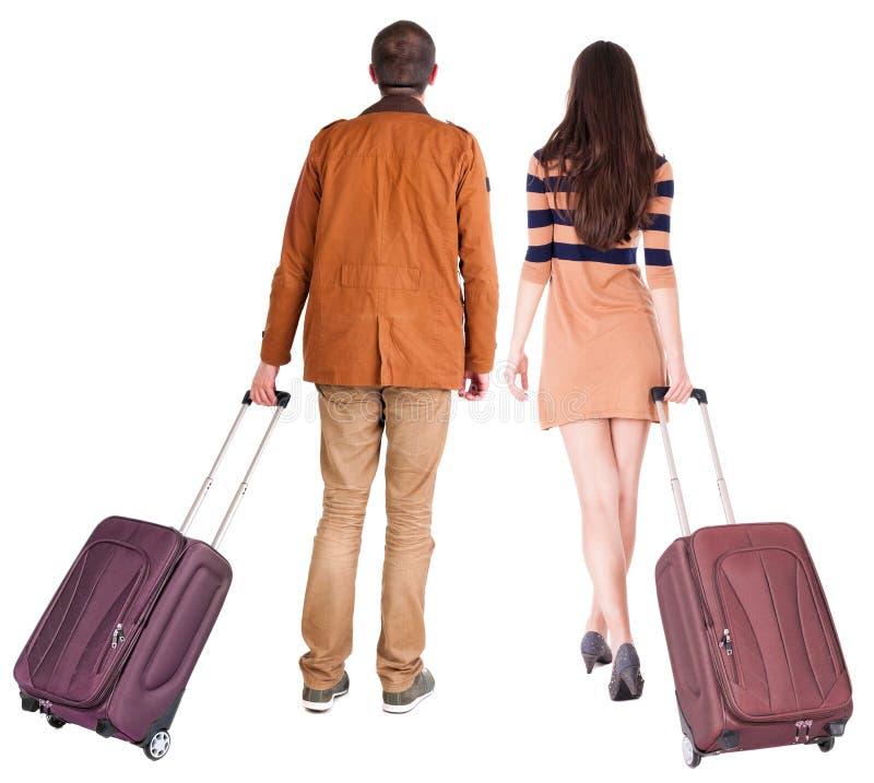 Hintere Ansicht von gehenden Paaren mit Koffer lizenzfreie stockfotografie