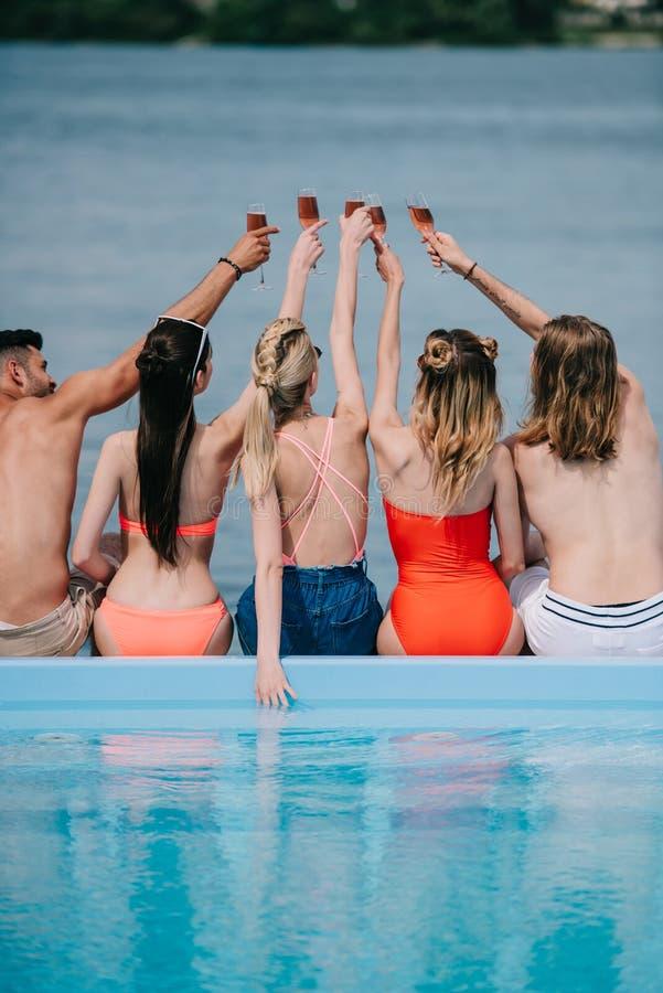 hintere Ansicht von jungen Männern und von Frauen, die Gläser Wein beim Sitzen nahe Pool klirren lizenzfreie stockfotos