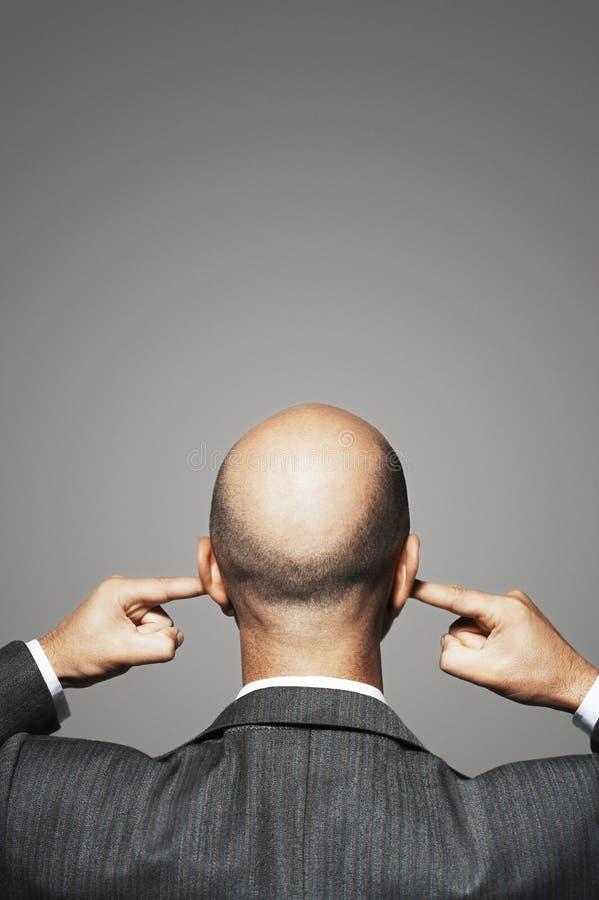 Hintere Ansicht von kahlen Geschäftsmann-With Fingers In-Ohren stockfotografie