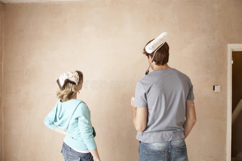 Hintere Ansicht von Paaren mit der Farben-Rolle, die Wand betrachtet stockbild
