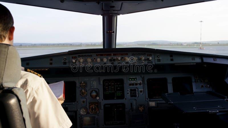 Hintere Ansicht von Pilotfunktionierenden Kontrollen des Geschäftsflugzeugs Captain im Flugzeugcockpit und bereiten sich für Flug stockfotos