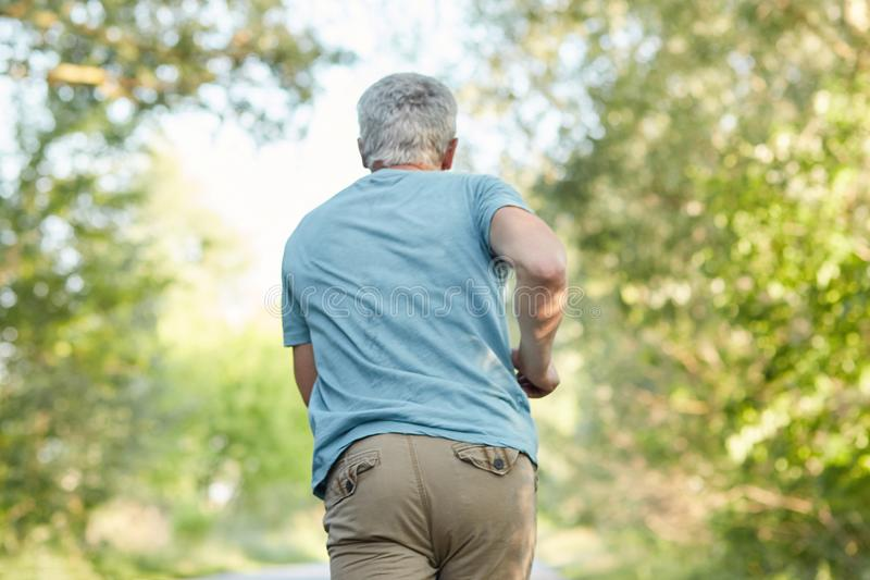 Hintere Ansicht von reifen männlichen joggs draußen, hat Morgengymnastik, genießt sonnigen Tag und Frischluft, seiend in der Bewe stockbild