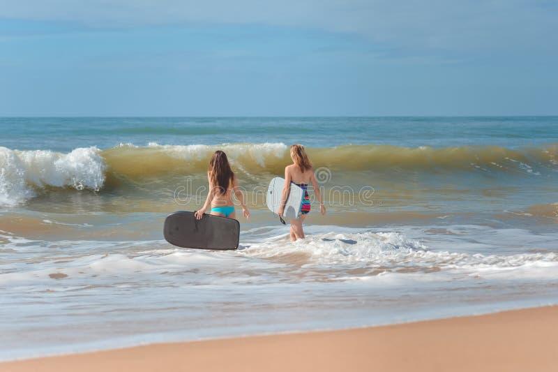 Hintere Ansicht von schönen jungen Frauen mit Surfbrettern stockfotografie