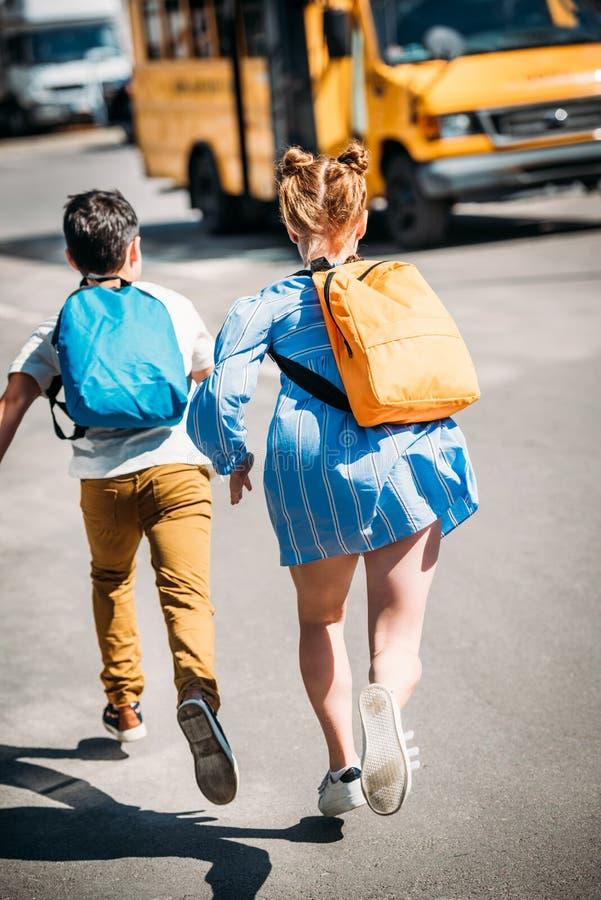 hintere Ansicht von Schülern mit den Rucksäcken, die zu laufen stockfotos