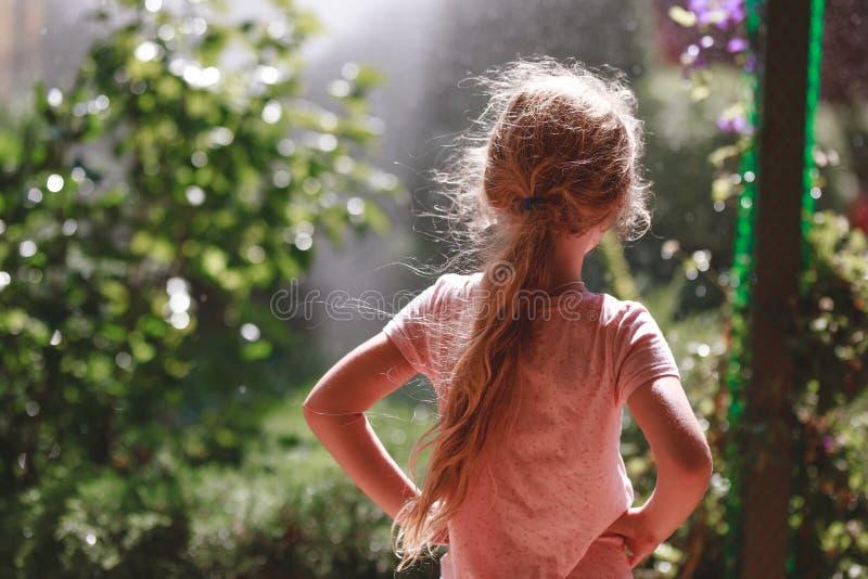 Hintere Ansicht von sieben Jahren tragenden Pyjamas des alten blonden Mädchens, die am frühen Morgen im Hausgarten im Freien steh lizenzfreie stockbilder