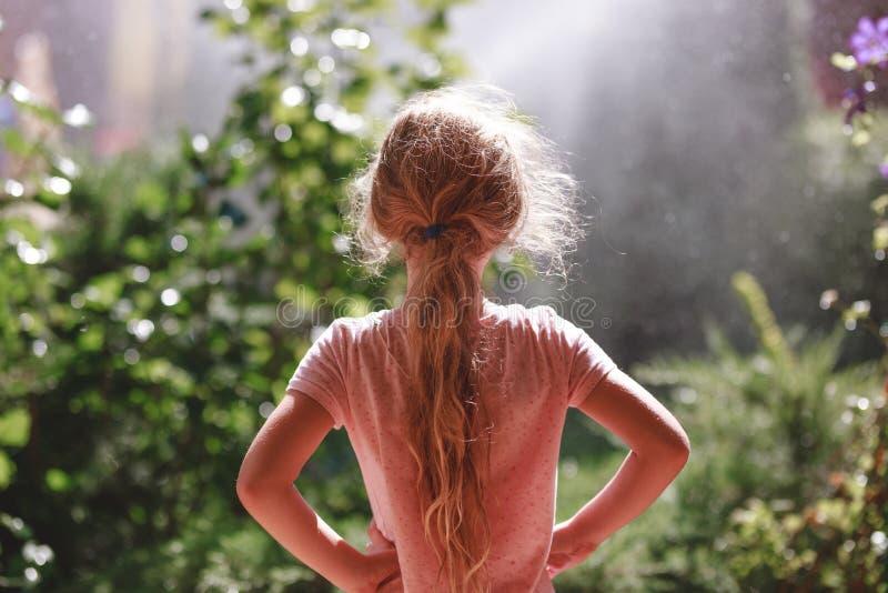 Hintere Ansicht von sieben Jahren tragenden Pyjamas des alten blonden Mädchens, die am frühen Morgen im Hausgarten im Freien steh lizenzfreie stockfotos