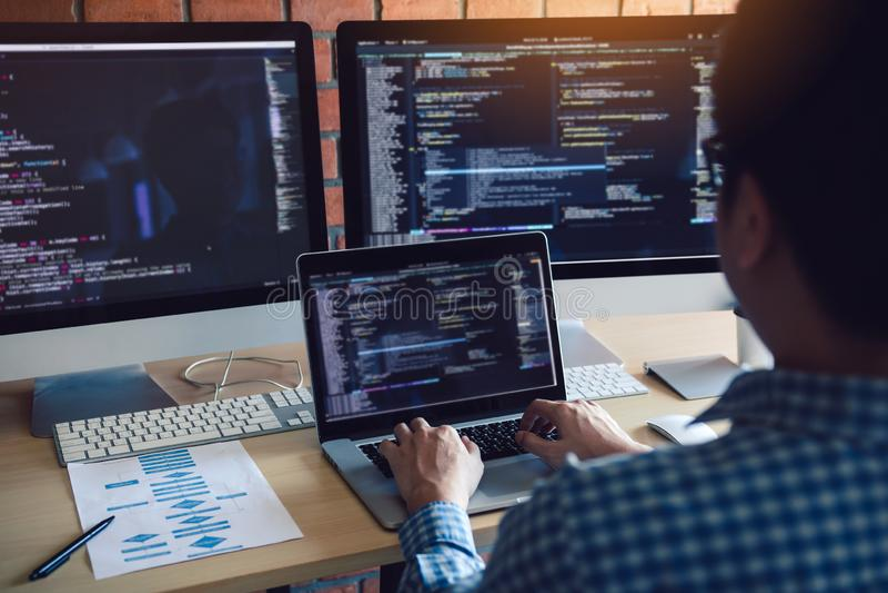 Hintere Ansicht von Softwareentwicklern sitzt ernste analysierende Daten auf dem Bildschirm stockbilder