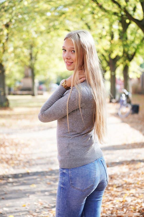 Hintere Ansicht von tragenden Jeans der jungen Frau und von Drehenkopf der Strickjacke herum lizenzfreies stockbild