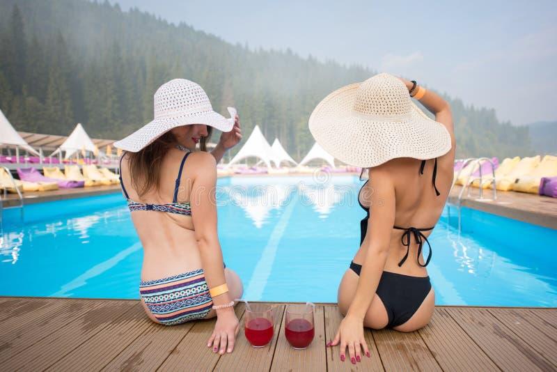 Hintere Ansicht von zwei Frauen, die in den Hüten sitzen am Rand des Swimmingpools mit Cocktails auf dem Hintergrund von Wäldern  lizenzfreie stockbilder