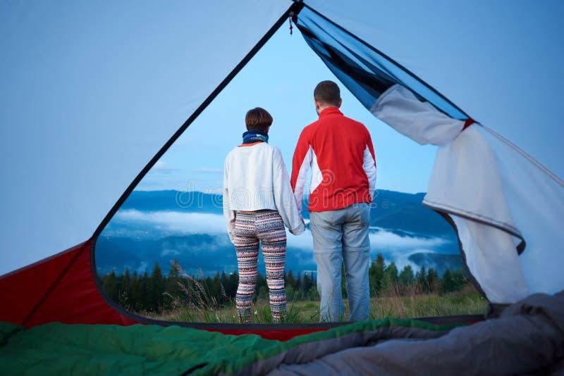 Hintere Ansicht von zwei Händchenhalten der jungen Leute genießen Morgenlandschaft von Bergen stockfotos