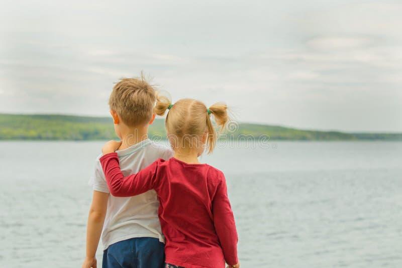 Hintere Ansicht von zwei liitle Kindern, Junge und Mädchen, umarmend auf einem See SH lizenzfreie stockfotos