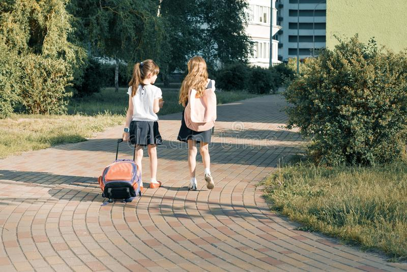 Hintere Ansicht von zwei Schulmädchenfreundingrundschülern, die mit Schultasche im Yard gehen lizenzfreie stockbilder