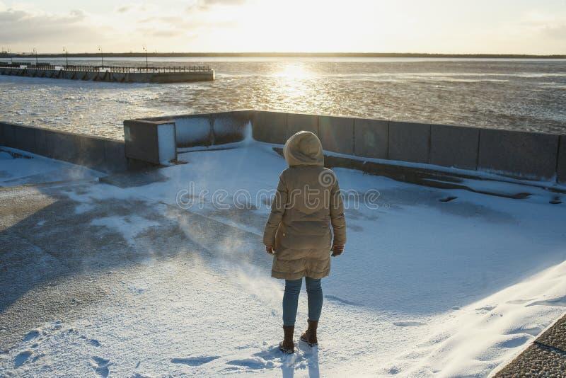 Hintere Ansichtfrau in einer Winterjacke mit einer Haubenstellung auf dem Damm von einem einfrierenden Fluss im Winter blizzard stockfoto