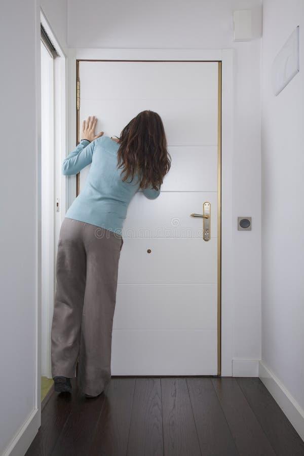 Hintere Frau, die Guckloch betrachtet lizenzfreies stockbild