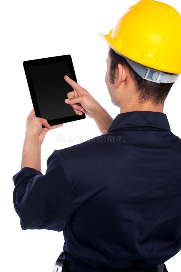 Hintere Haltung des funktionierenden Tablettengerätes der Arbeitskraft stockfotografie