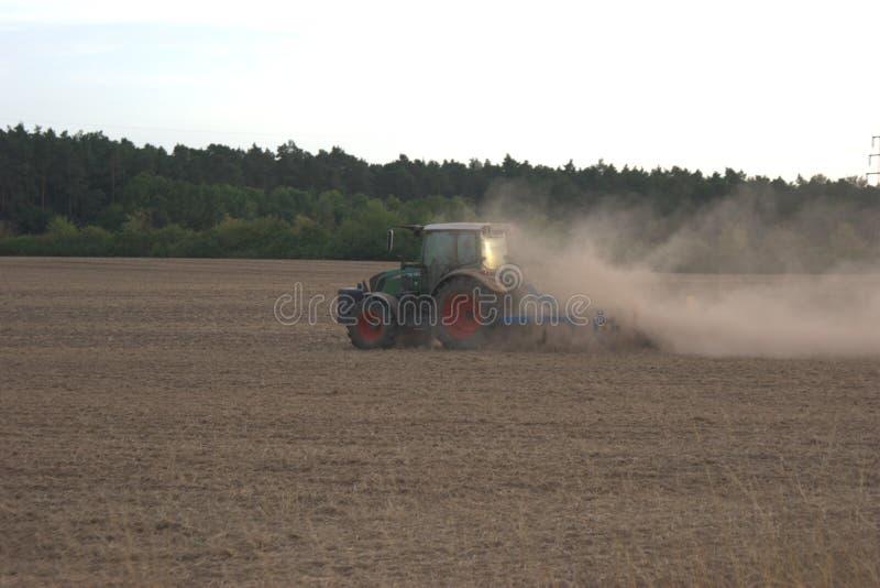 Hintere linke Seitenansicht eines landwirtschaftlichen Traktors, der ein Feld während der Dürre von 2018 in Deutschland eggt lizenzfreies stockbild