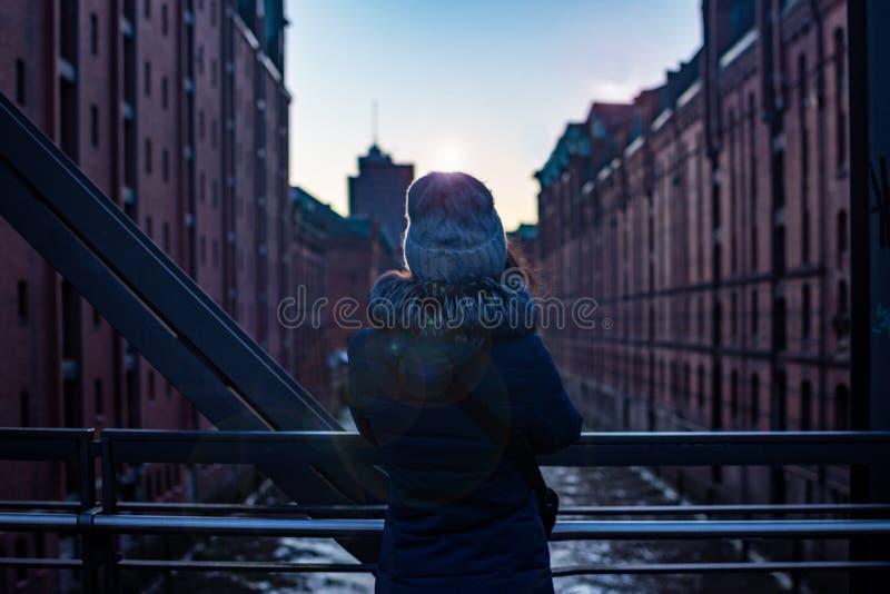 Hintere Mädchenansicht Mädchenstellung auf der Brücke, die das moderne Gebäude der Sonnenuntergang und das weiche Licht aufpasst  lizenzfreie stockfotos