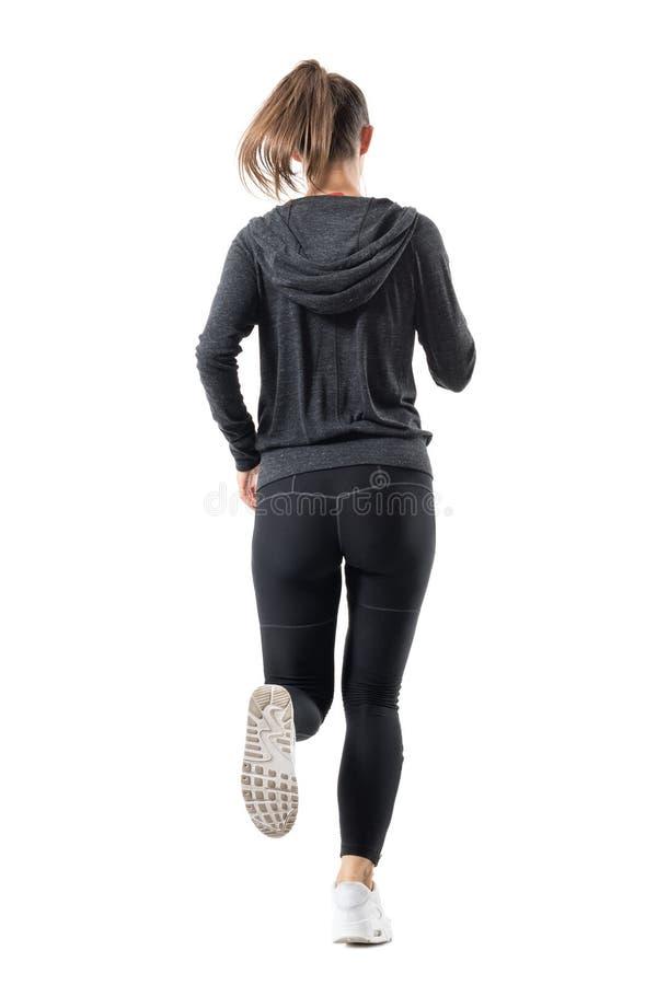 Hintere Rückseitenansicht des weiblichen Läufers im mit Kapuze Sweatshirt, das weg läuft stockfoto