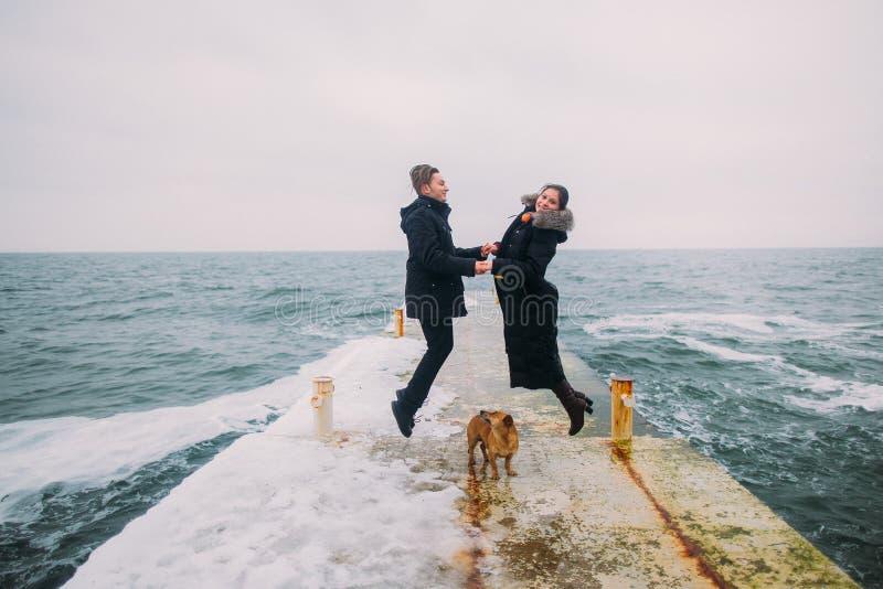 Hintere romantische Ansicht eines jungen Paares, das zusammen mit kleinem Hund geht und Spaß auf entsteintem Pier während des reg stockbilder
