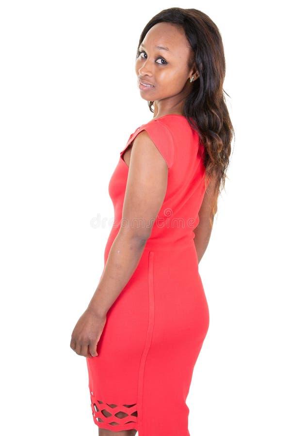 Hintere hintere Seitenansicht der hübschen Frau des jungen Afroamerikaners lokalisiert im Weiß im roten Modekleid von hinten stockbild