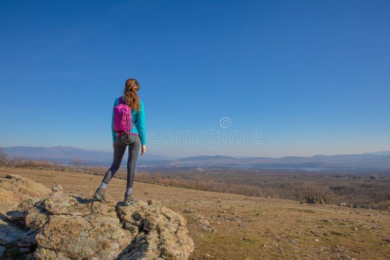 Hintere Wandererfrauenstellung auf Felsen in Madrid-Berg, der das Tal betrachtet stockfotos
