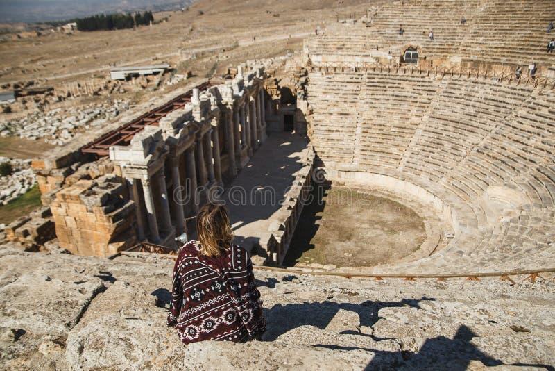 Hinterer Ansichtfrauenreisender, der betrachtet, überraschend am Amphitheater in altem Hierapolis, Pamukkale, die Türkei lizenzfreie stockbilder