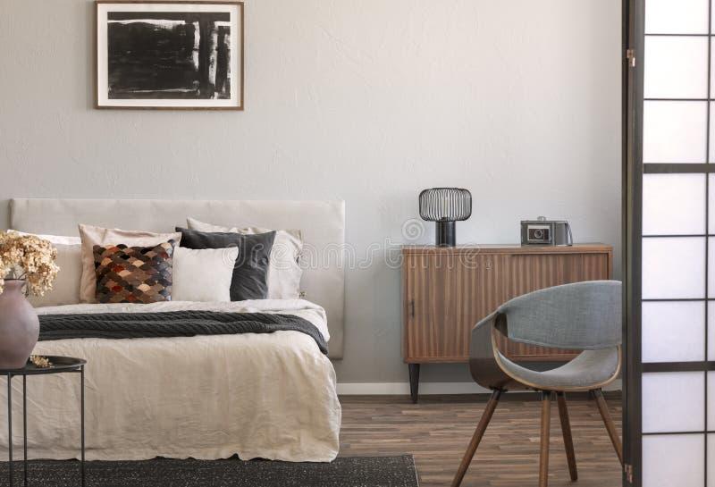 Hinterer Stuhl des modischen Flügels im fantastischen Schlafzimmer Innen mit eleganten Möbeln lizenzfreie stockfotos