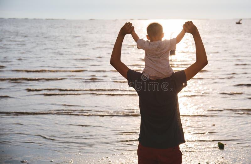 Hinterer Vatervati- und -Babysohnlebensstil, der auf Schultern sitzt stockfotografie