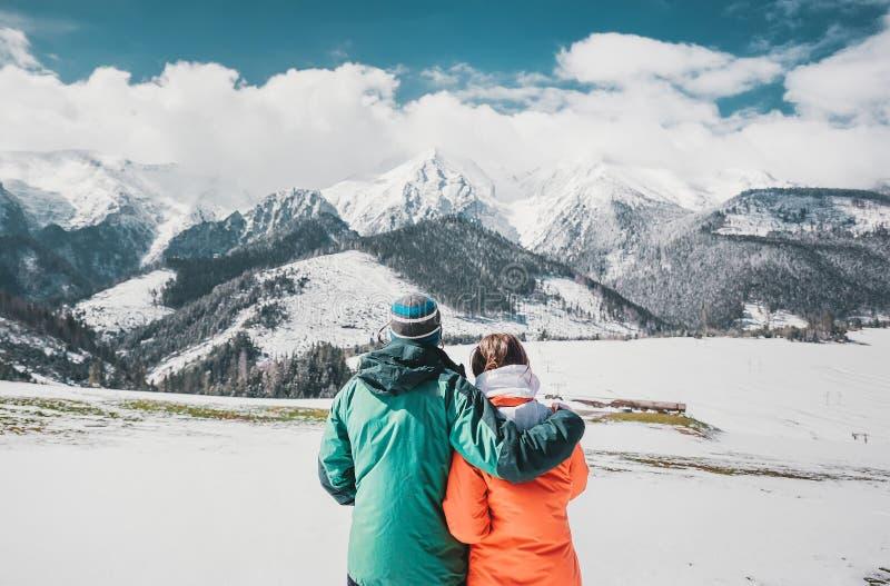 Hinteres Ansichtfoto von den jungen liebevollen Paaren, die über Winterbergen umarmen Betrachten von Bergen stockfotos