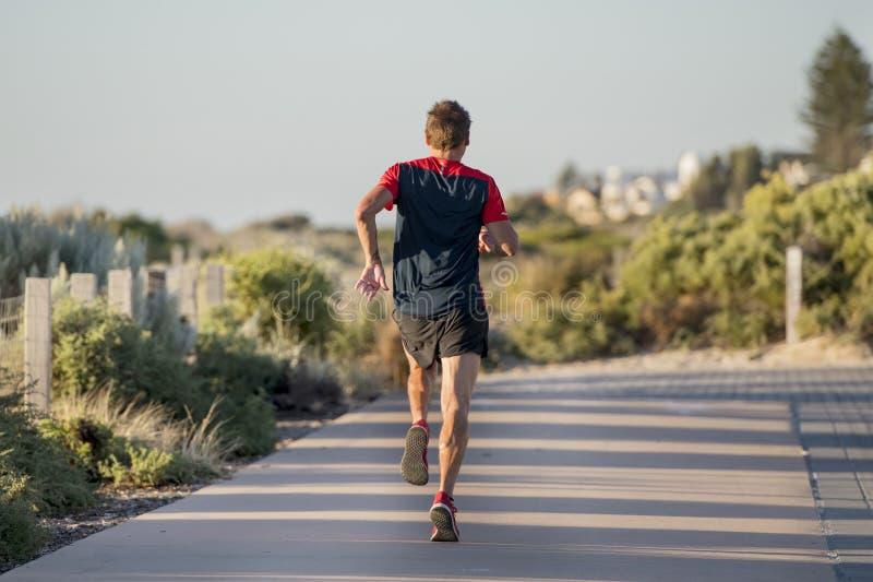 Hinteres Porträt des jungen Sportläufermannes mit Sitz und starkem gesundem Körpertraining auf weg von Straßenbahn in laufendem T stockbilder
