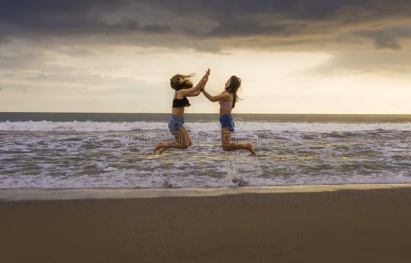 Hinteres Porträt von zwei glücklich und attraktives Freundinhändchenhalten der jungen Frauen auf dem Strand, der zum Meer unter s stockbilder