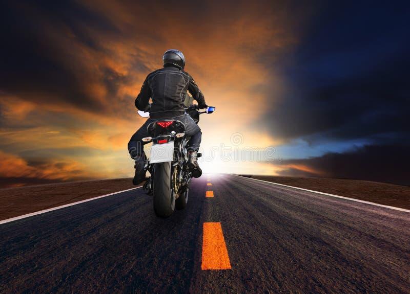 Hinteres veiw des jungen Mannes großes Motorrad auf Asphaltstraße gegen schönen düsteren Himmel reiten stockfotografie