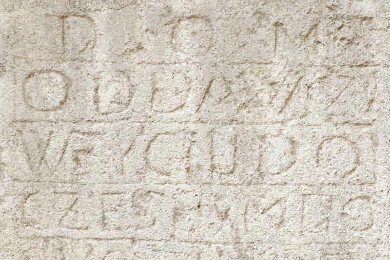 Hintergründe und Beschaffenheitskonzept Verblaßte lateinische Buchstaben auf einem alten Stein Front View lizenzfreie stockfotografie