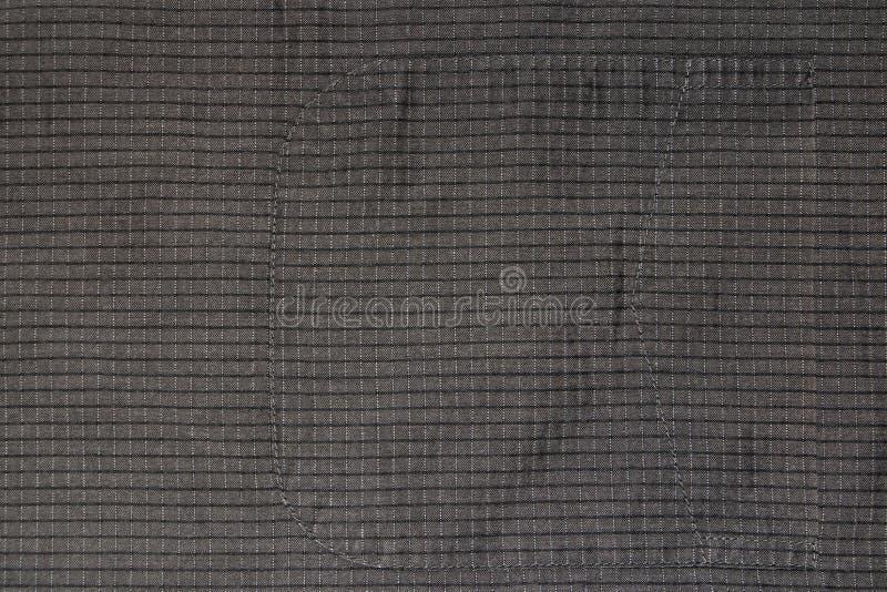 Hintergrund, Beschaffenheit des alten Baumwollgewebees in einem Käfig mit einer genähten Tasche lizenzfreie stockfotografie