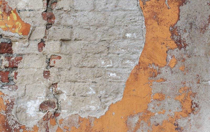 Hintergrund der alten gebrochenen Backsteinmauer mit besprühtem Zementputz und Reste der Farbe stockbild