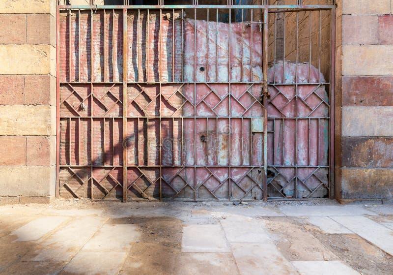 Hintergrund des antiken Schmiedeeisentors des alten Schmutzes mit geometrischen Musterverzierungen und sone Ziegelsteinwand lizenzfreie stockfotos