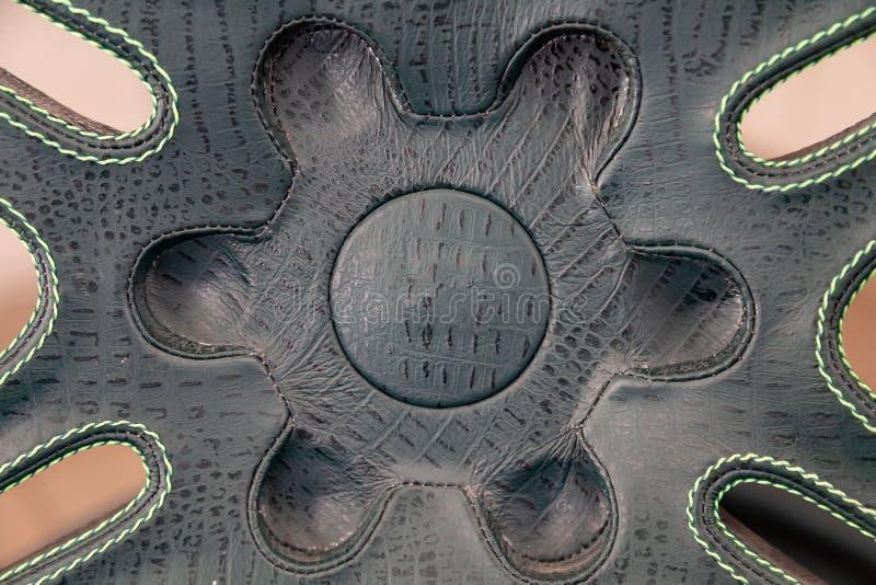 Hintergrund des grünen Leders mit den schwarzen Flecken geklebt auf dem Element der komplexen Form und der kontrastierenden Naht lizenzfreie stockfotos
